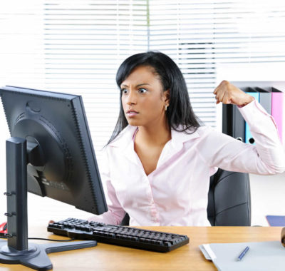 Lady sat at computer looking over whelmed