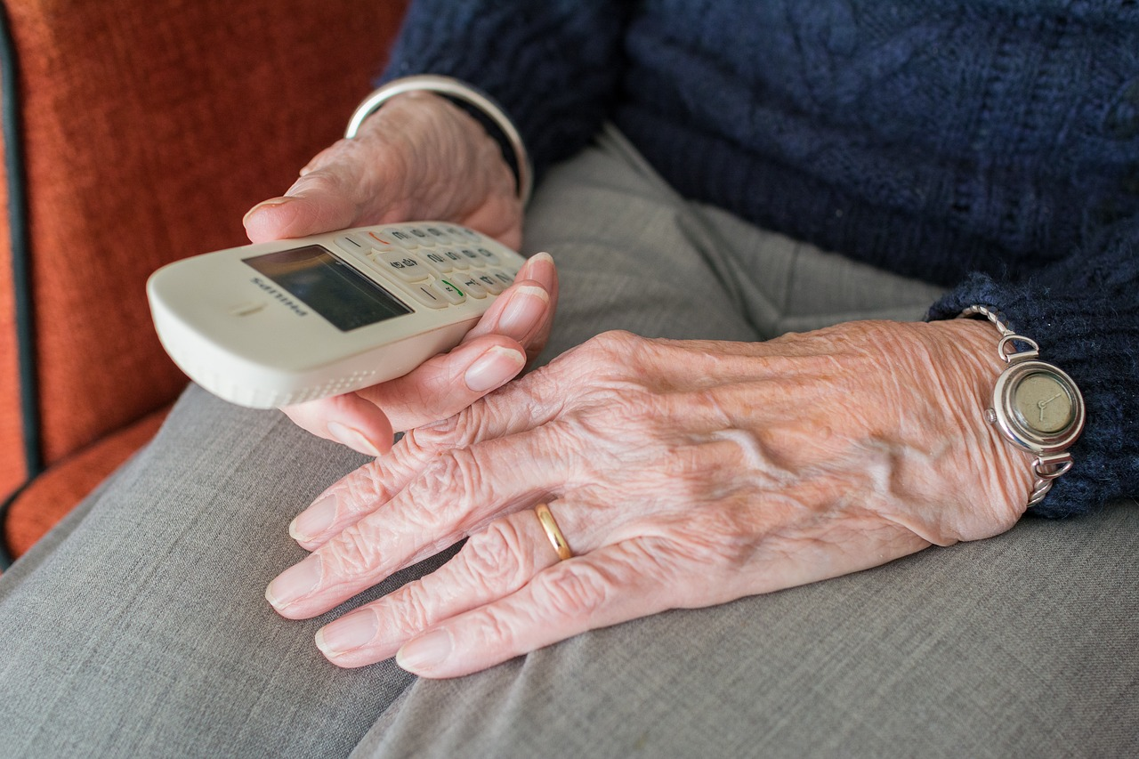 Elderly woman holding a white home phone