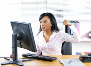 Woman sat at computer looking over whelmed