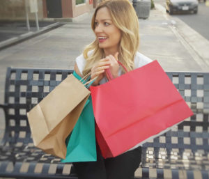 Young woman holding shopping bags looking happy