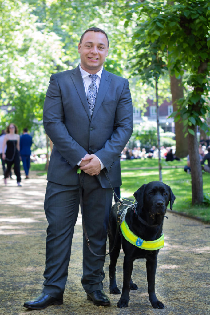 Photo of Daniel and his guide dog Zodiac in a leafy park