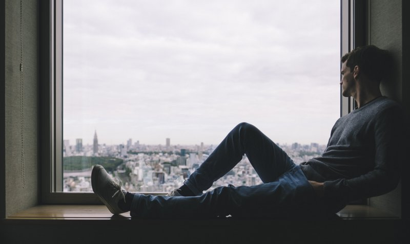 Man sat in a window looking over a city with depressed body language