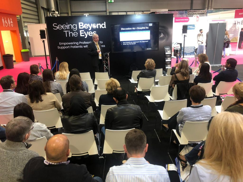 Peter Black on stage presenting to attendees in the Seeing Beyond the Eyes Zone at Optrafair