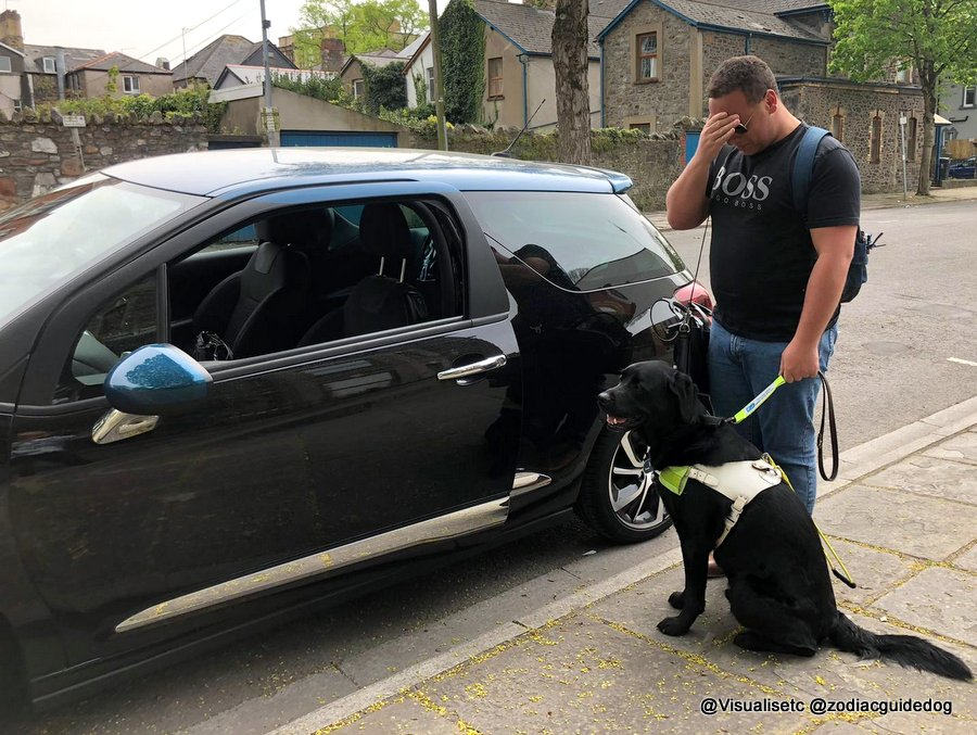 Daniel, with head in hands,  and his guide dog Zodiac being refused entry to a taxi.