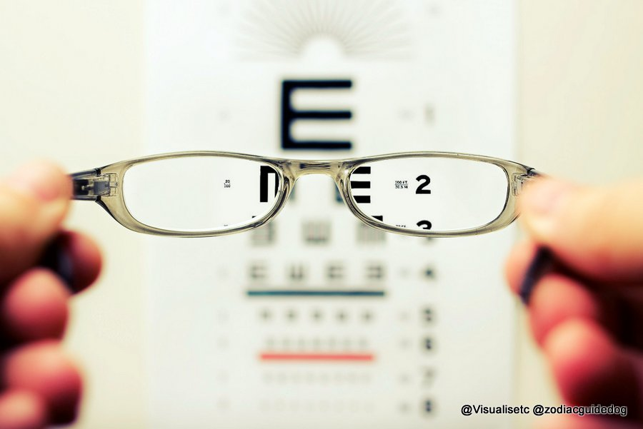 Looking through specs at an eye test chart