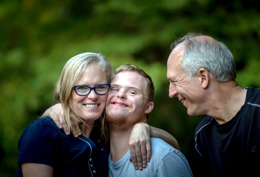 Young man smiling and hugging his parents