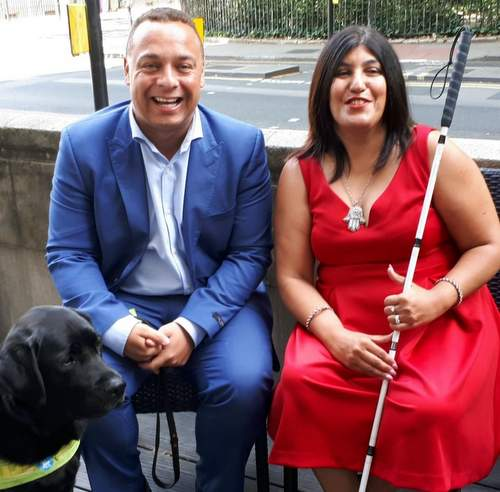 Man and woman laughing with guide dog
