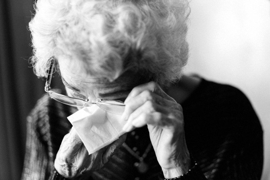 Older lady wiping her eye with a tissue