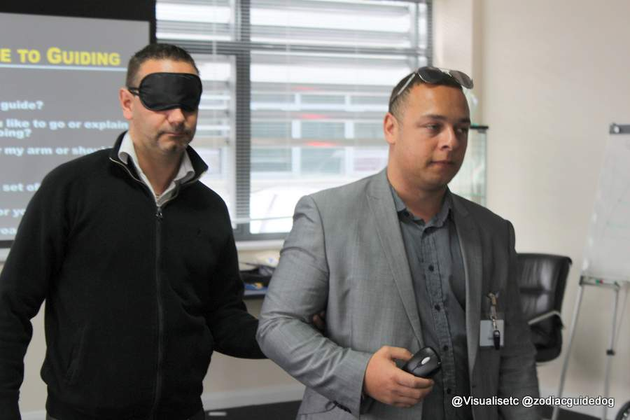 A Visualiase trainer guiding delegate who is wearing a blindfold