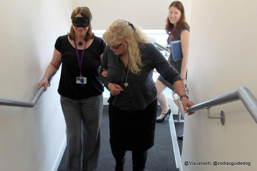 One of our female trainers guiding another lady who is wearing a blindfold up some stairs. Our Visual Impairment Awareness Training will enable you to do the same safely and effectively.