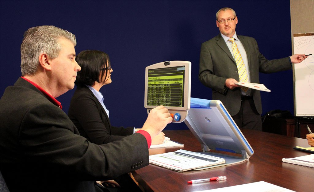Employee with sight loss in a meeting using assistive technology to read a document