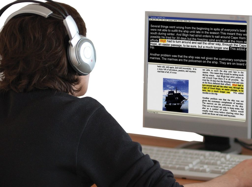 Employee using text to speech software using headphones and magnified text