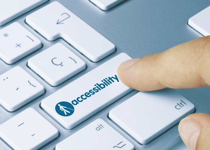 Finger pressing a laptop key entitled accessibility - it also has a logo of a person using a white cane on it