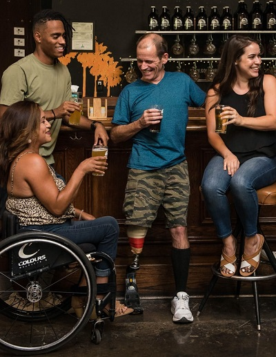 A group of friends smiling and having fun in a pub. It includes a woman in a wheelchair and a man with a prosthetic leg. We use this image in training.