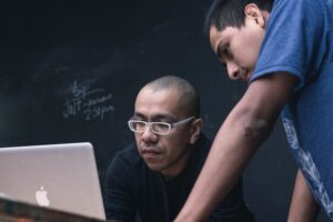 Two men looking at a laptop
